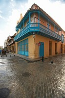 Turquoise shutters on a historic landmark building and cobblestone street in Old Havana
