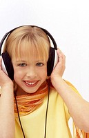 A young girl listens to music with large earphones