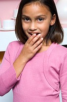 Portrait of a young girl dressed in pink covering her mouth