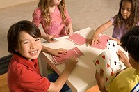 Portrait of kids playing cards