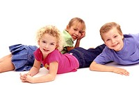 Three young children laying on the floor smiling
