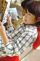 Portrait of Hispanic and Asian boy reading comic books