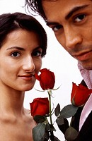 Portrait of an attractive Hispanic couple holding roses