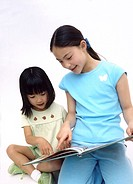 Portrait of two young girls reading together
