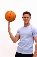 Caucasian male spinning basketball on finger
