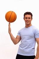 Caucasian male spinning basketball on finger