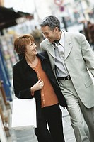 Mature couple walking on city sidewalk, smiling at each other