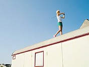 Female golfer on caravan roof