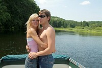 young couple tenderly embracing on boat