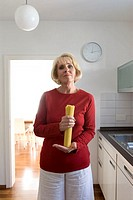 portrait of mature woman with spaghetti in kitchen