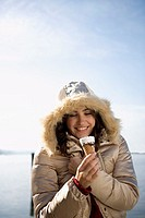 portrait of young woman looking forward to having an ice cream in winter