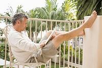 Man Reading Book on Balcony