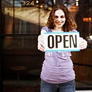 Young Woman Holding ´Open´ Sign Outside Store