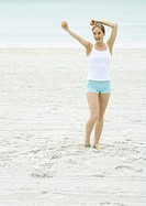 Young woman standing on beach with arms in air