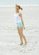 Young woman standing on beach, stretching arm (thumbnail)