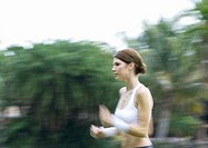 Young woman running outdoors, blurred motion