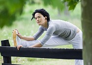 Young woman stretching leg on wooden fence