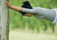 Young woman stretching against tree trunk