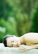 Woman lying on towel, eyes closed