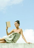 Woman sitting wrapped in towel, reading book, sky in background