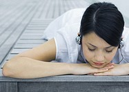 Woman lying on deck, listening to headphones