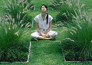 Woman sitting in ornamental garden with eyes closed