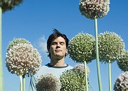 Man with eyes closed and allium flowers