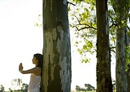 Woman standing with hands in prayer position, leaning against tree