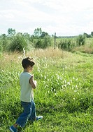 Boy walking in grass, side view