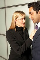 Side profile of a businesswoman adjusting a businessman's tie