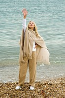 Mid adult woman standing on the beach and waving her hand