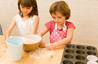 Close-up of two girls kneading flour