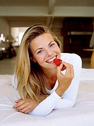 Portrait of a young woman laying on the bed and holding a strawberry