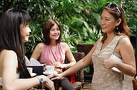 Three women talking at outdoor garden cafe