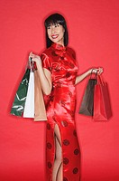 Woman in red cheongsam, against red wall, carrying shopping bags