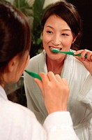 Woman looking at mirror, brushing teeth