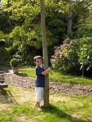 Boy hugging a tree in garden