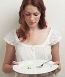 Young woman holding a plate with three peas on it
