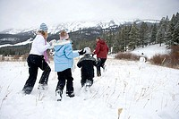 Mature woman with her son and daughter throwing snowballs at a mature man