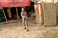 a nagababa sadhu covered with ashes  doing his exercise next to the latrine of his akhara, the Juna Akhara
