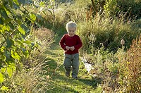 Small trubled boy walking in the garden Bornholm 2005