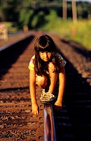 A girl positioning on a railway track while looking at camera