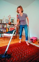 Young woman vacuuming the floor