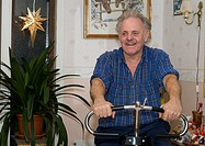 An old man practise his exercise bike at home