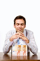 Young man with house of Euro notes, eyes closed
