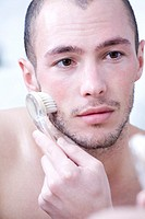 Man massaging face with brush