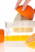 Woman preparing orange juice, close-up