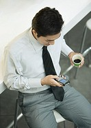 Executive holding cup of coffee and checking cell phone
