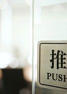 'Push' sign on door in English and Chinese