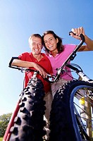 Young couple on bicycle, smiling, low angle view, portrait